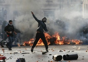 A protester throws a stone at riot police during a march in central Athens
